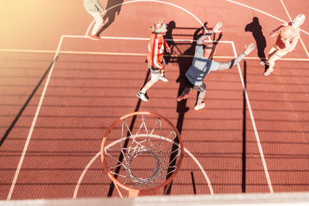 During a match. Top view of a basketball basket with people playing under it Stock Photo