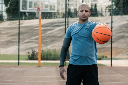 My passion. Handsome well built man standing on the basketball court while looking at you