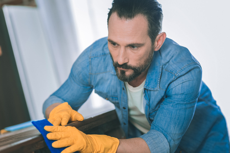 Do not bother me. Handsome male person wearing rubber gloves while wiping dust at home Stockfoto