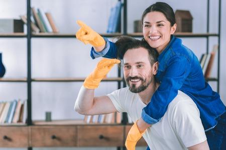 Schauen Sie in eine Richtung. Glücklicher brünette Mann, der seine Frau auf dem Rücken hält, während er seinen rechten Arm hebt Standard-Bild