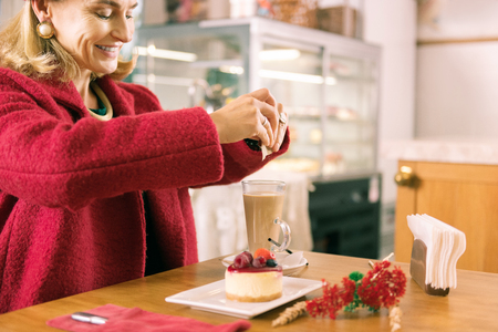 Smiling woman. Smiling mature fashionable woman with facial wrinkles putting sugar in her coffee