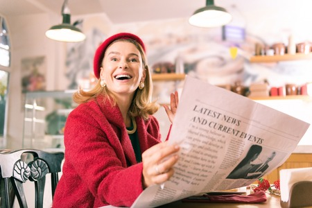 Cheerful woman. Cheerful blonde-haired mature woman wearing red beret waving her friend seeing him Stock Photo