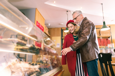 Choosing desserts. Loving stylish couple of mature man and woman choosing French desserts in nice bakery
