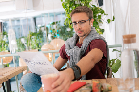 Cafe and news. Dark-haired handsome stylish man sitting in vegan cafe and reading morning news