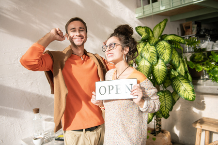 Happy man. Stylish man wearing orange sweater feeling happy after opening restaurant with wife