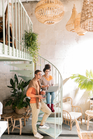 Own restaurant. Successful hard-working couple sitting on nice stairs in their own restaurant