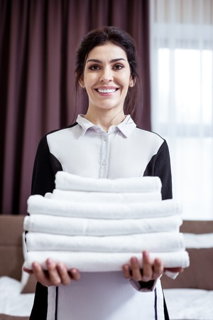 Very clean. Delighted joyful maid looking at you while holding white towels