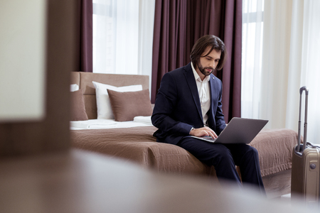 Work issues. Serious professional businessman working on a laptop while sitting on the bed in his hotel room