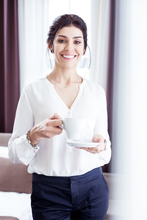 Beginning of the day. Nice confident businesswoman drinking a cup of coffee while starting her working day