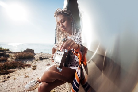 Scarf on hand. Stylish female appealing musician wearing scarf on her hand playing the guitar sitting in trailer