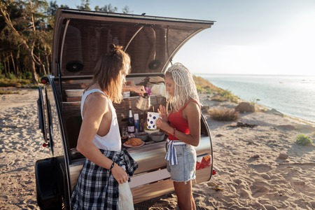 Pouring tea. Caring loving man with tattoo pouring some hot tea for girlfriend living in trailer together Imagens