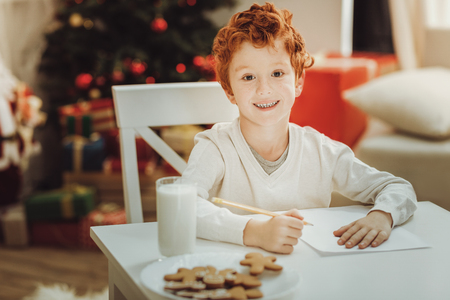 Christmas tradition. Positive child keeping smile on his face and sitting at the table while going to drink milk