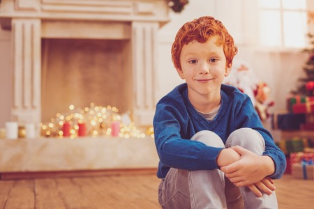Cozy ambience. Cute ginger-haired boy sitting on the floor with his knees pulled up to his chest and posing for the camera while waiting for start of Christmas celebration Stock Photo
