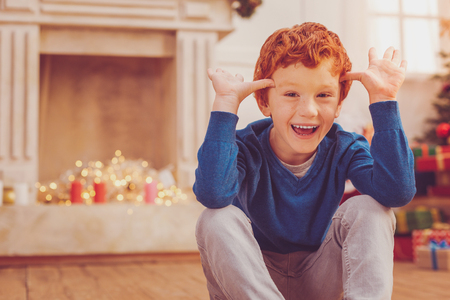 Playful mood. Joyful preteen boy sitting on the floor in a room decorated for Christmas and laughing while touching his temples with his thumbs in a teasing way