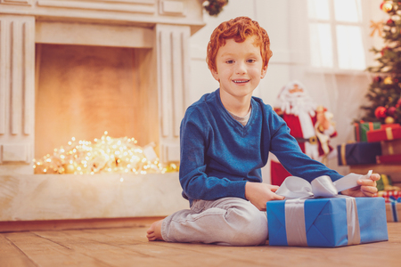 Pleasant present. Upbeat red-haired preteen boy sitting on the floor in front of a chimney and posing for the camera with his Christmas present
