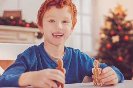 Imagination play. Adorable red-haired preteen boy smiling at the camera cheerfully while playing with two gingerbread men Stock Photo