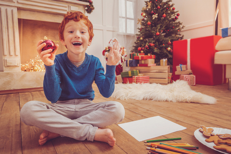 Love drawing. Pleasant upbeat preteen boy sitting cross-legged on the floor of the living room and being excited about drawing a Christmas bauble in his hand