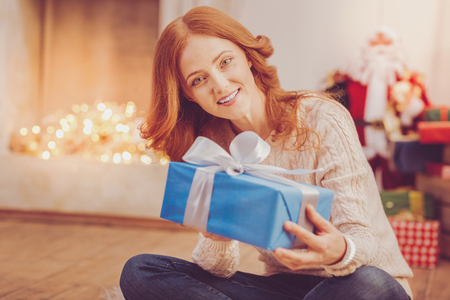 I love presents. Beautiful upbeat red-haired woman sitting cross-legged on the floor and posing for the camera while holding a blue box with a Christmas gift Stock fotó