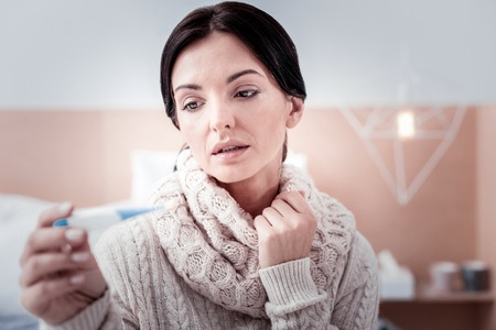 Caught a cold. Upset beautiful woman holding thermometer while feeling unhappy with the temperature Stock Photo