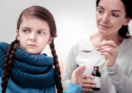 One more spoon. Close up of little upset child looking away while her mother holding cough syrup and giving it to her child