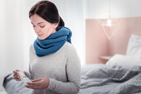Unhealthy. Portrait of young woman with blue warm scarf looking down while keeping a box with pills in both hands