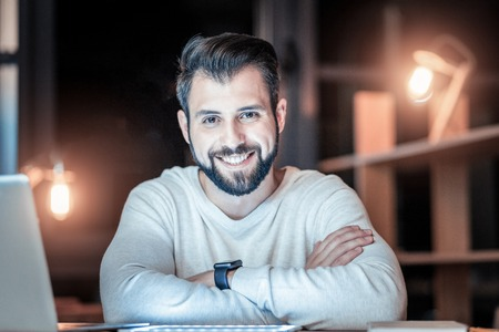 Being satisfied. Attractive man showing his smile after hard work and holding crossed arms on the table