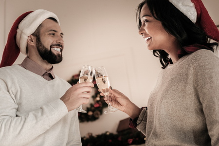 Lets celebrate. Handsome male person expressing positivity while looking at his girlfriend and going to drink champagne
