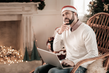 Deep in thoughts. Concentrated man sitting in rocking-chair and holding laptop on knees while creating plan