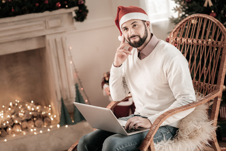 Have a dream. Attractive bearded man holding laptop on knees and touching cheek while looking aside