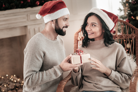 It is for you. Handsome bearded man expressing positivity and holding box with present while standing near his girlfriend Stock Photo