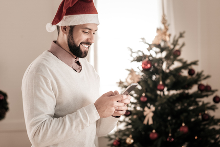 Good news. Handsome man standing in semi position and holding telephone in both hands while reading message Stock Photo