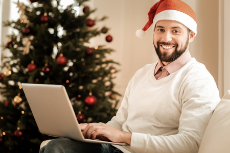 Ready for celebration. Happy positive bearded man smiling and holding his laptop while wearing a Santa hat