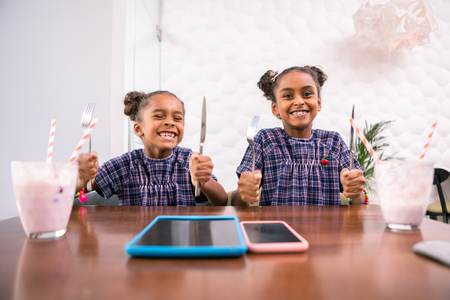 Knives and forks. Beaming laughing stylish siblings holding knives and forks waiting for lunch food Фото со стока