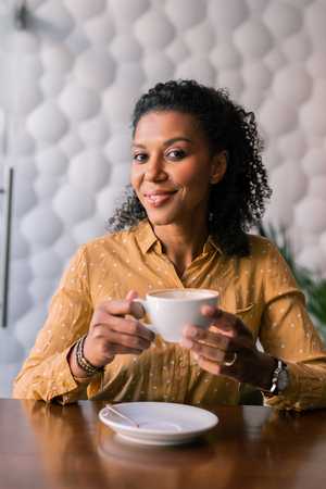 Drink coffee. Stylish appealing woman wearing accessories and yellow spotted blouse drinking coffee