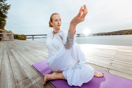 Half Lord of the Fishes Pose. Relaxed woman practising yoga asanas