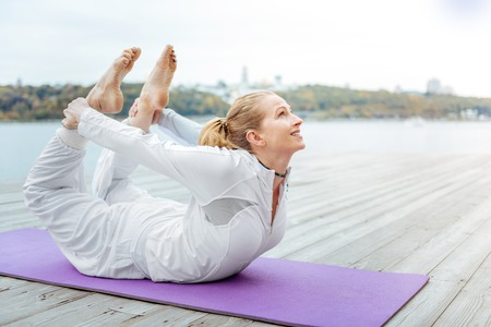 Woman in Bow Pose. Motivated woman doing morning exercises Standard-Bild