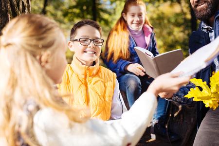 Mit einer Klasse. Fröhlicher glücklicher Junge, der lächelt, während er mit seiner Klasse eine Tour im Wald macht