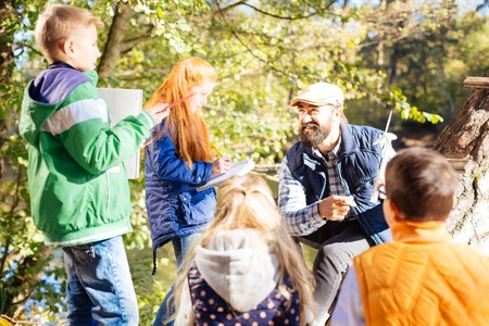 Forest keeper. Joyful bearded man talking to young kids while telling them about windmills