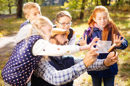 Curious class. Cute happy children surrounding their teacher while helping him to take photos Reklamní fotografie