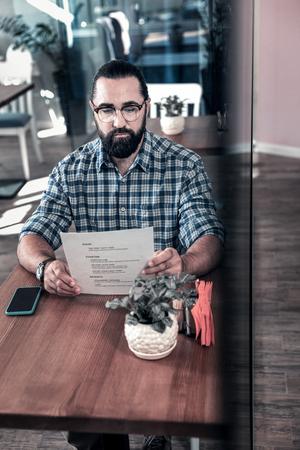 Look at menu. Successful bearded businessman looking at the menu coming to cafeteria having break Standard-Bild