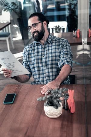 Choosing dish. Pleasant bearded man wearing glasses having hesitation choosing main dish in the restaurant Standard-Bild