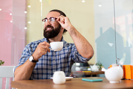 Coffee break. Successful bearded pleasant businessman wearing glasses having coffee break in cafeteria Banco de Imagens