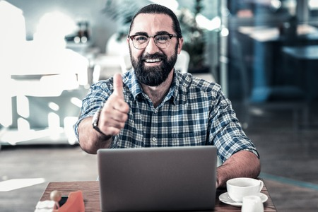 Approving work. Bearded dark-eyed businessman wearing glasses approving the work of his employees