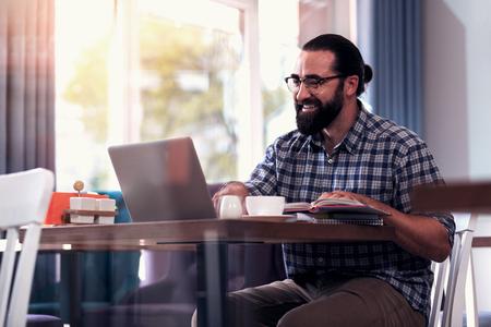 Documents on laptop. Beaming pleasant mature man reading important documents on laptop before the meeting Reklamní fotografie
