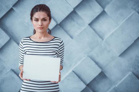 Toile pour le texte. Belle femme bouleversée tenant une affiche blanche claire faisant la promotion d'idées et de suggestions Banque d'images