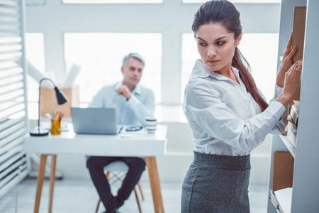 Moment de travail suspect. Jeune femme soupçonnant son supérieur en séduction alors qu'il était assis au bureau Banque d'images