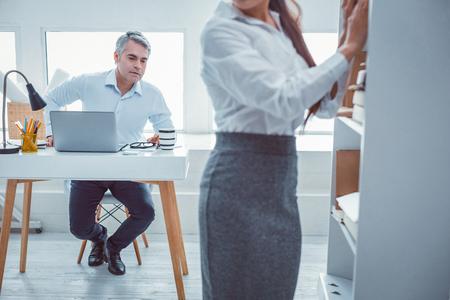 Homme désagréable. Supérieur aux cheveux gris regardant son jeune collègue de la tête aux pieds au travail