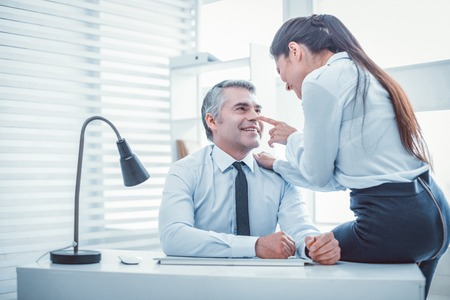 Smiling boss. Long-haired beautiful female sitting on the table and flirting with her boss Stock Photo
