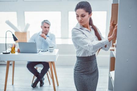 Situation désagréable. Belle travailleuse en forme se sentant anxieuse à propos de son patron qui la regarde dans le dos