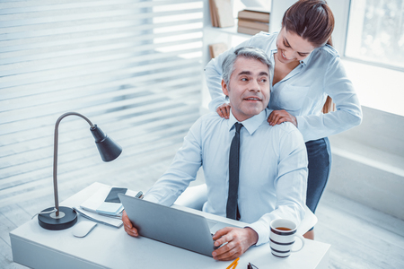 Joyful partners. Happy surprised boss receiving a massage from his good-looking fit secretary during their workday Stock Photo